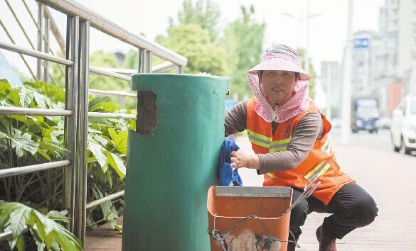 株洲女环卫工擦净垃圾桶内胆