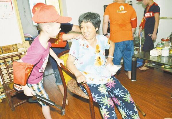 小朋友给易爹爹的老伴按摩 记者 谢慧/摄 8月11日上午,来自株洲沿河社区的18名孩子集结在一起,开展了一场别样的暑假体验活动担任一天社区180服务热线的志愿者,为社区孤寡、行动不便的老人当家,帮他们买菜、做家务,陪他们唠嗑。 这些小小志愿者最小的7岁,最大的14岁。株洲沿河社区党支部书记曾江华说,每周,孩子们都会为社区老人服务一天。